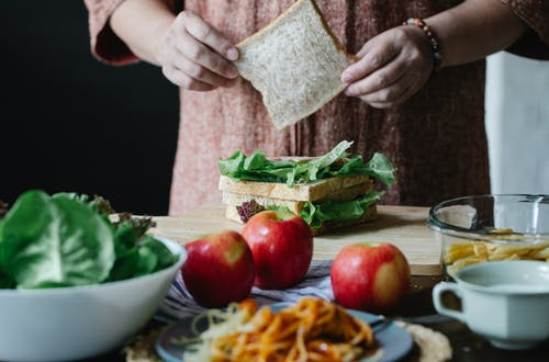 Unrecognizable female cook putting slice of bread on lettuce while standing at table and making sandwich in kitchen during breakfast time