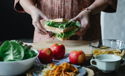 Unrecognizable female standing at table with apples and cutting board with sandwich with lettuce in hands in kitchen on breakfast time