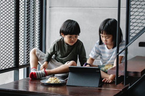 Asian kids watching video on tablet near stairs