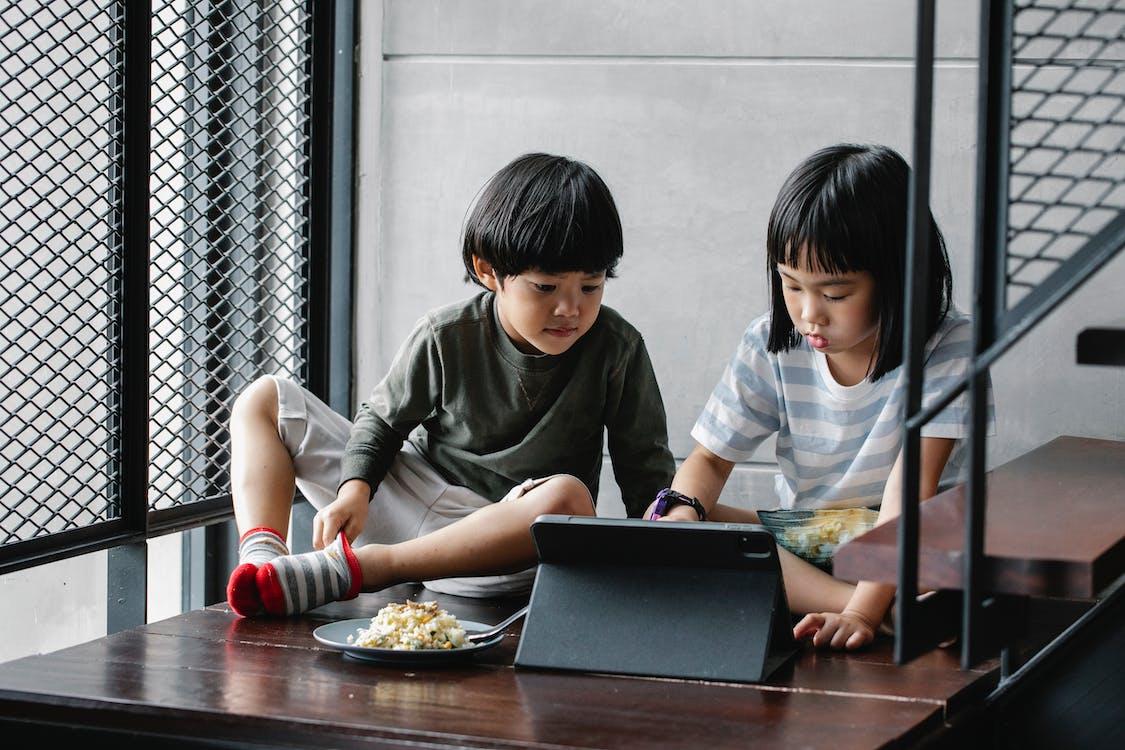 亞洲孩子在樓梯附近的平板電腦上觀看視頻