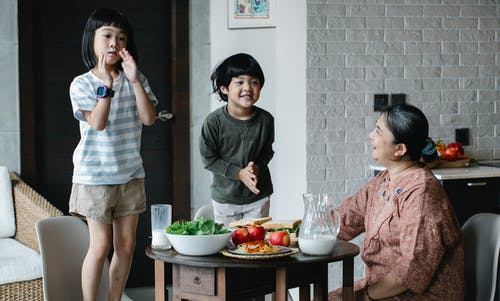 Asian grandmother sitting at served table during breakfast in kitchen while looking at Asian boy and girl having fun together