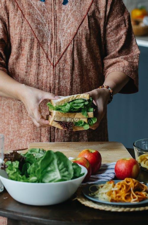 Crop woman making sandwich in kitchen