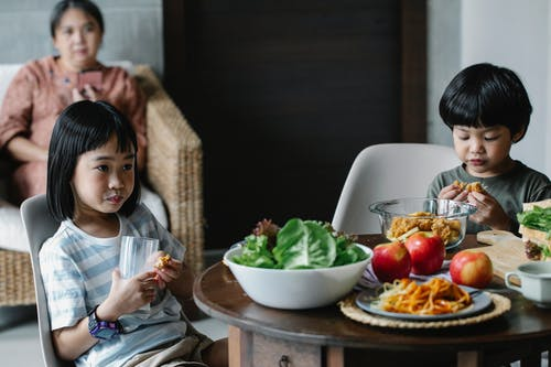 Calm Asian boy and girl sitting at served table while drinking milk during breakfast in kitchen with blurred grandmother on background