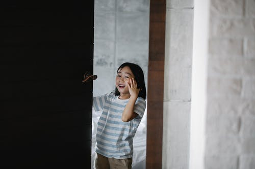 Cheerful Asian kid looking at camera while standing near wooden door and white brick wall with hand on cheek in flat
