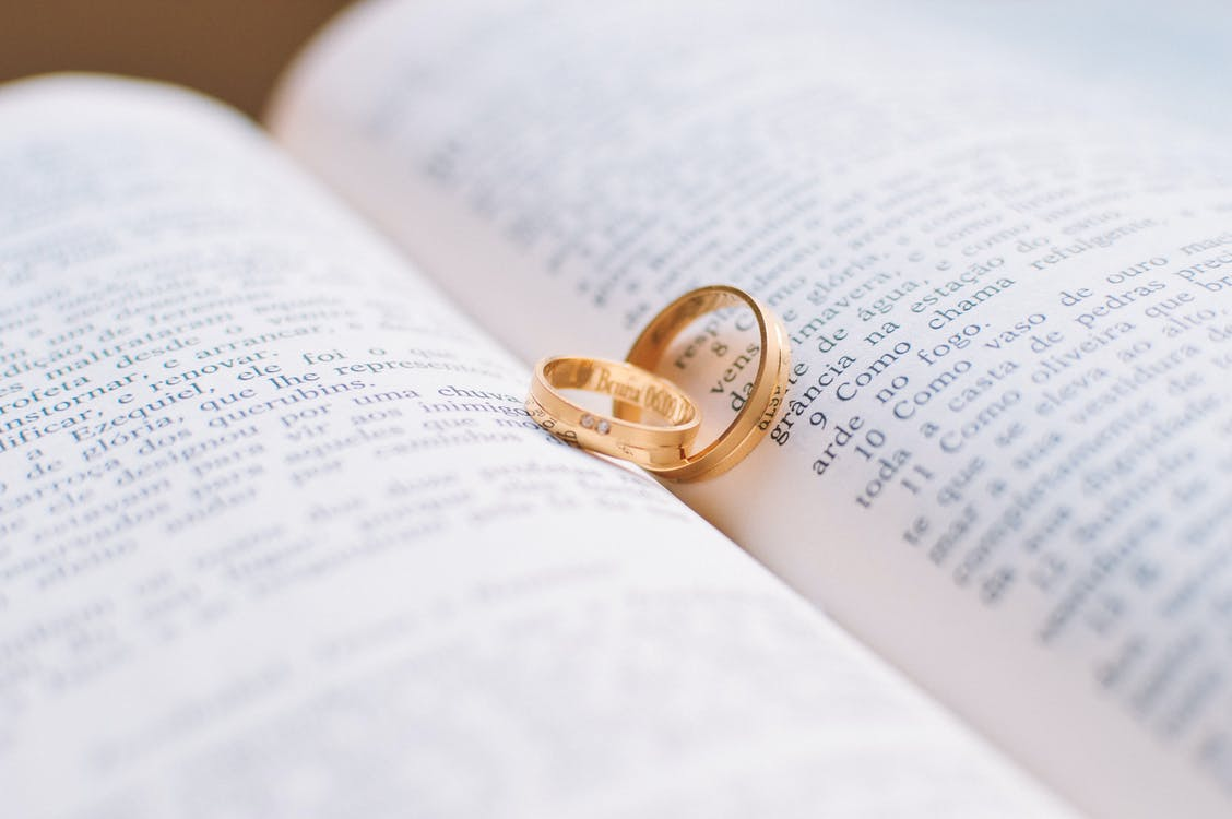 Two Gold-colored Wedding Bands on Book Page
