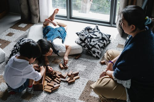 From above of Asian boy and girl playing with wooden blocks near window on floor in living room with grandmother