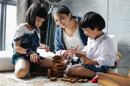 Happy grandmother sitting on floor with Asian boy and girl while playing with wooden blocks and building tower in living room near window