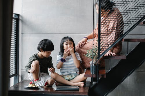 Senior ethnic woman with grandchildren relaxing on stairway at home