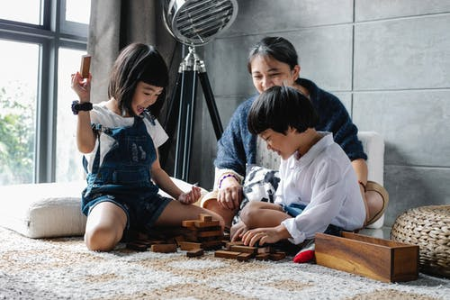 Cheerful little Asian siblings sitting on carpet with grandmother and playing tower game during weekend at home
