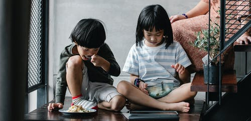 Asian children watching video on tablet and having snack at home