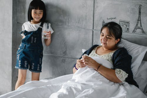 Adorable Asian little girl holding glass of water while standing near senior ill grandmother lying in bed in morning