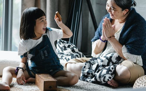 Cheerful woman with granddaughter playing tower game at home