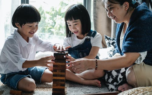 Full body of happy ethnic little children with elderly grandmother sitting on floor and constructing wooden tower while playing board game at home