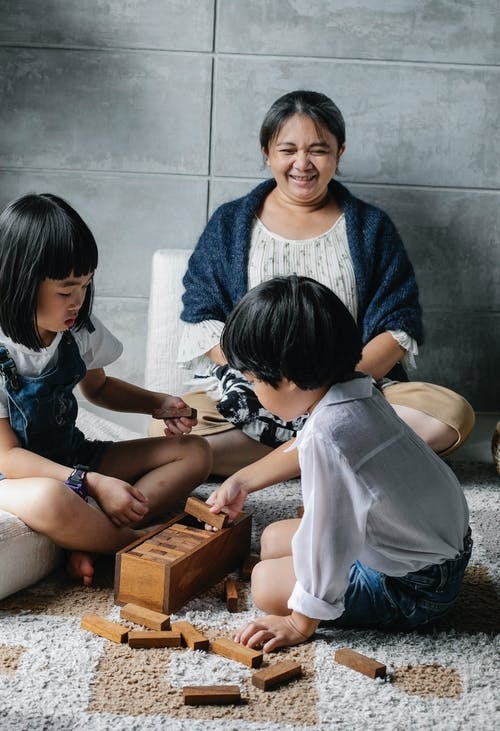 Happy elderly ethnic female looking at cute grandchildren playing board game sitting on carpet at home