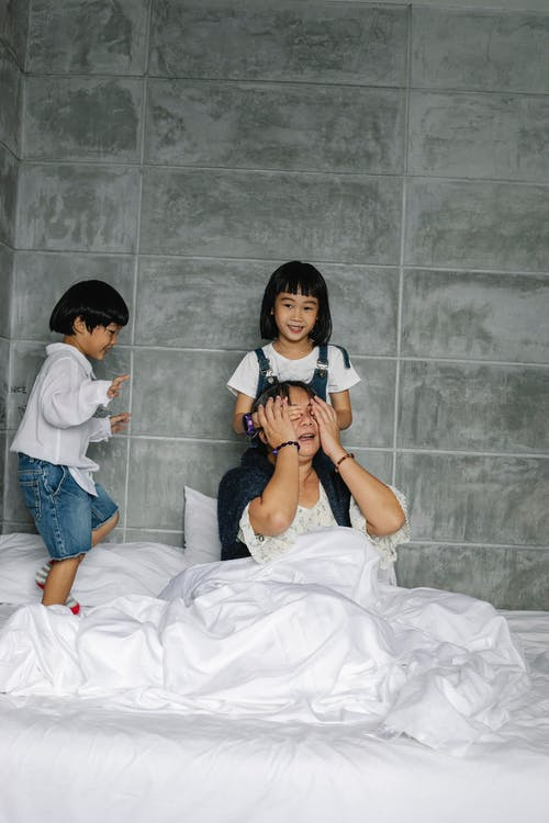 Excited ethnic kids having fun with grandmother on soft bed