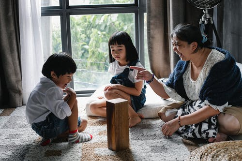 Content Asian children having fun with grandmother during game at home