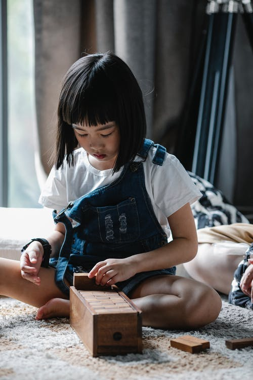 Attentive Asian little girl in jeans clothes sitting on carpet and picking up wooden pieces of board game in daylight at home