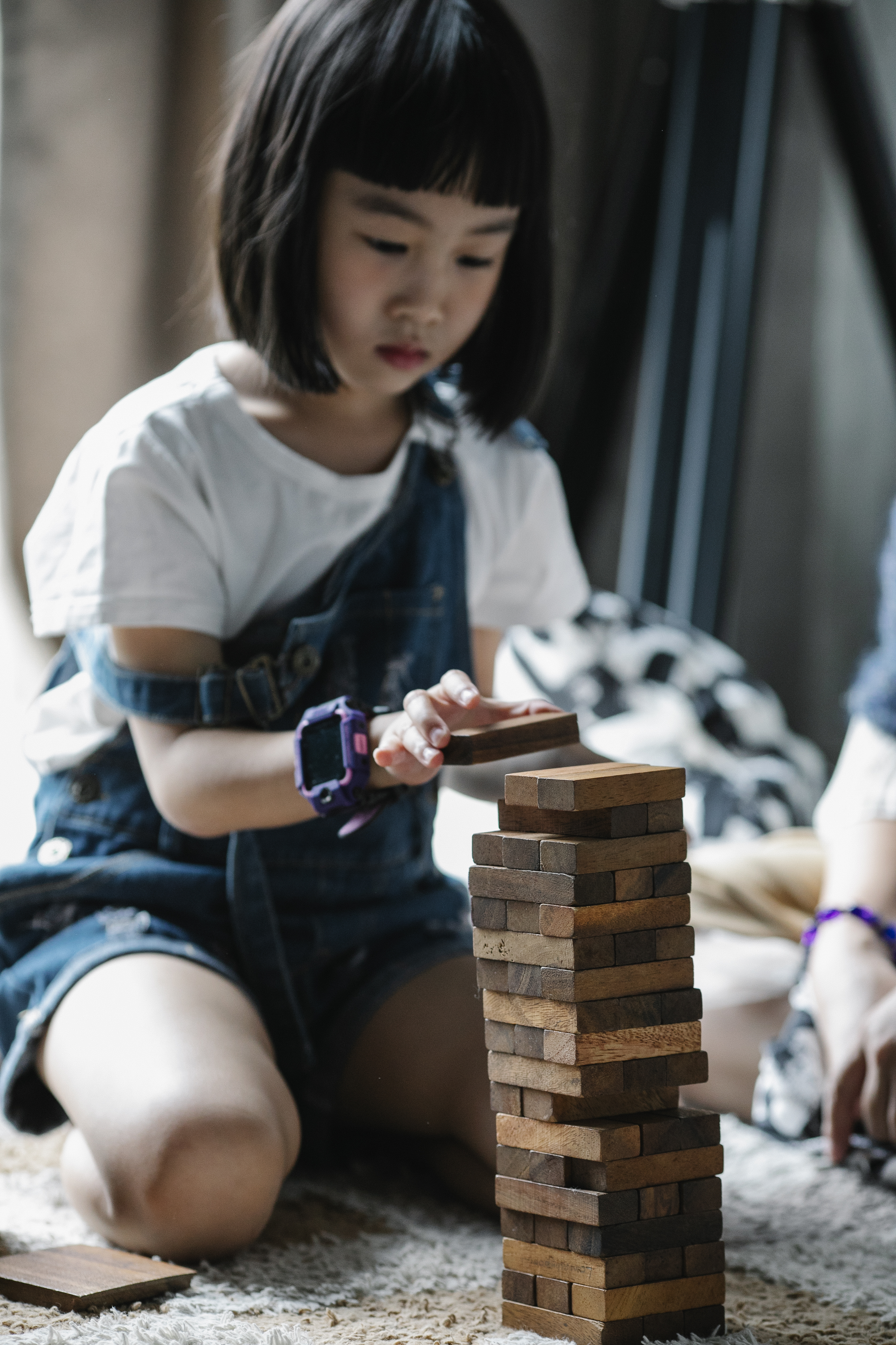 serious asian child playing with tower game sitting on carpet