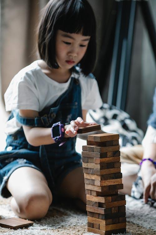 Grave Niño Asiático Jugando Con Juego De Torre Sentado En Una Alfombra