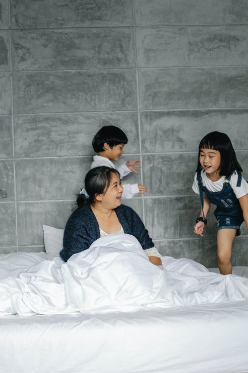 Active children running on bed around sitting grandmother