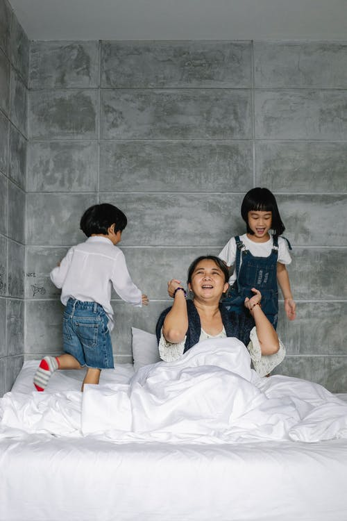 Funny ethnic little kids running on bed while playing with positive grandmother sitting under blanket in sunny morning