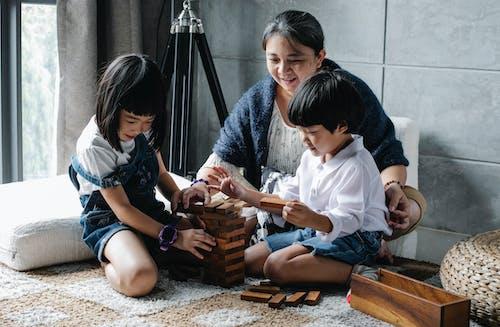 性格開朗的小民族兄弟姐妹在微笑的祖母的幫助下玩棋盤遊戲