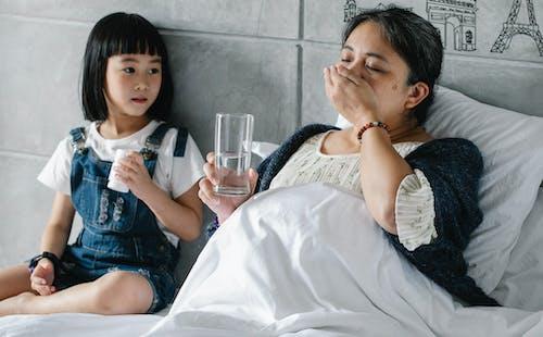 Больная этническая женщина принимает лекарства, лежа в постели рядом с очаровательной внучкой