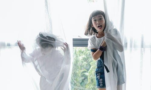Смешные этнические дети прячутся за занавеской, играя вместе дома