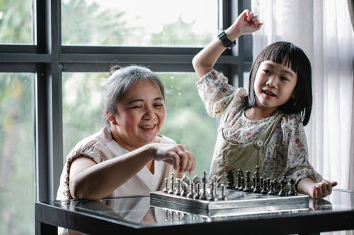 Happy little Asian girl with grandmother sitting at table and playing chess during weekend at home