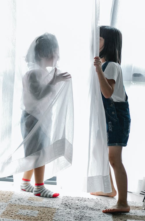 Side view of unrecognizable little siblings hiding behind curtains while playing together at home