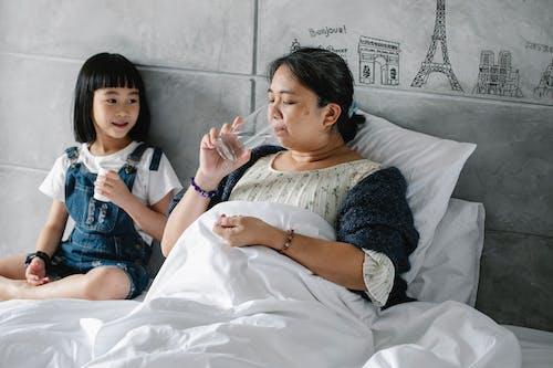 Очаровательный этнический ребенок дает таблетки нездоровой бабушке, пьющей воду в постели