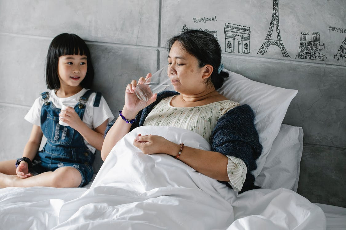 Adorable ethnic child giving pills to unhealthy grandmother drinking water in bed