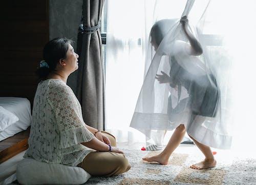 匿名的小女孩玩亞洲祖母坐在臥室的地板上