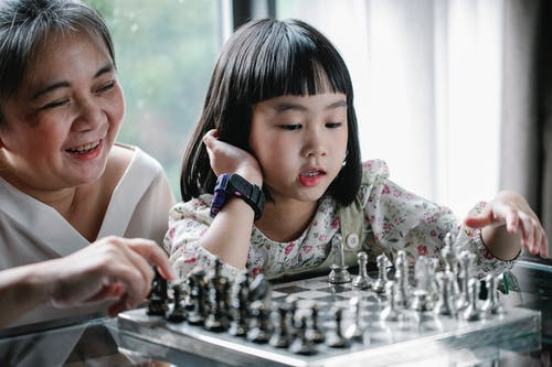 Adorable ethnic child doing move while playing chess with grandmother