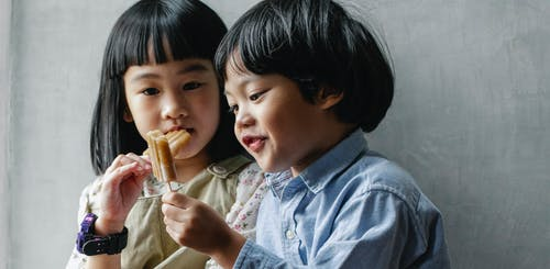 Adorable little Asian siblings with dark hair eating sweet yummy ice pop while standing near gray wall