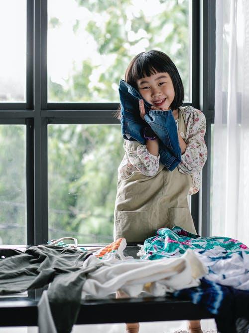 Happy ethnic kid choosing clothes at home
