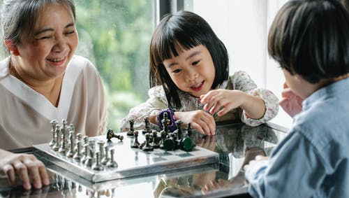 Crop cheerful elderly ethnic female helping adorable little grandchildren playing chess at table in light room