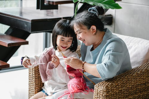 Cheerful senior Asian woman sitting in armchair and helping curious little granddaughter  to knit warm clothes with yarn in daylight