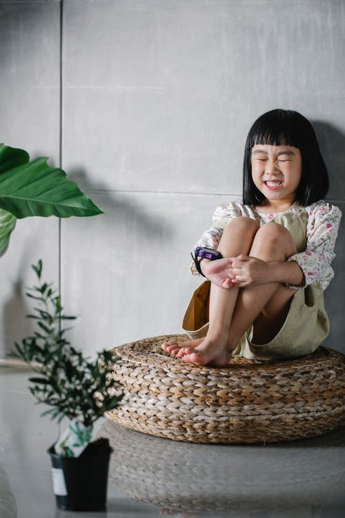 Full body of funny cute little Asian girl sitting on rattan round floor cushion with closed eyes