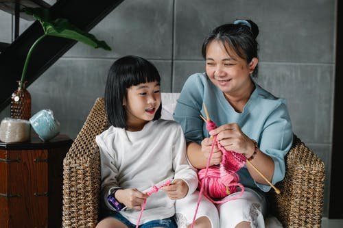 Content Asian child with grandmother sitting in armchair and knitting