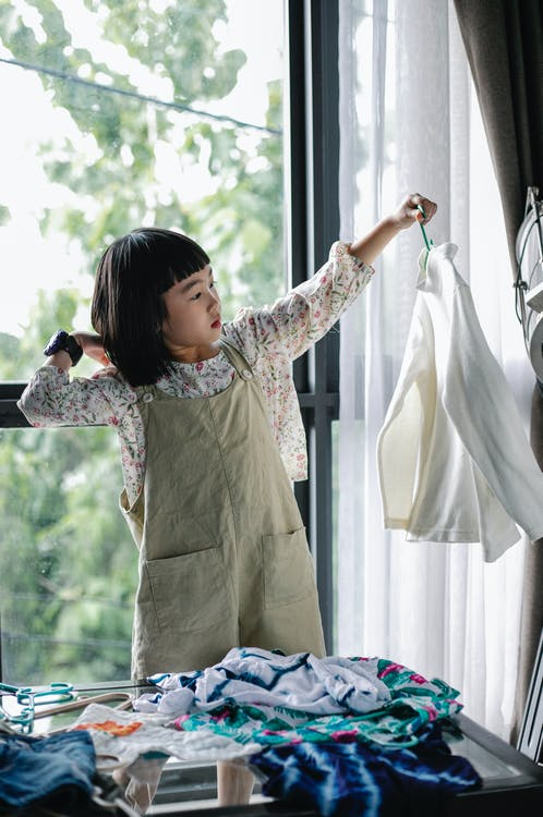 Adorable ethnic child sorting clothes in room