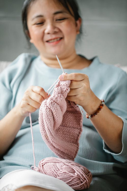 Crop positive elderly Asian woman using needles and pink yarn while knitting warm clothes at home