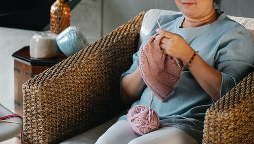 High angle of crop unrecognizable middle aged female in casual clothes sitting in stylish rattan armchair and knitting with wool yarn at home
