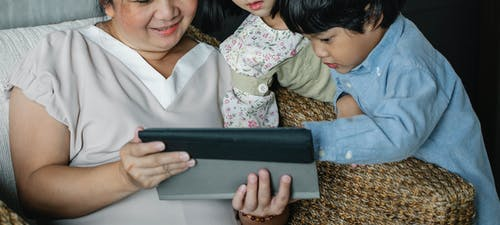 Anonymous Asian woman with grandchildren watching video on tablet