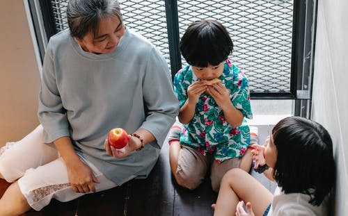 Adorable ethnic siblings eating fruits with grandmother at home