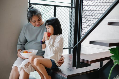 Kind senior ethnic granny cuddling adorable little granddaughter while sitting together on stairway at home and eating fresh ripe fruits