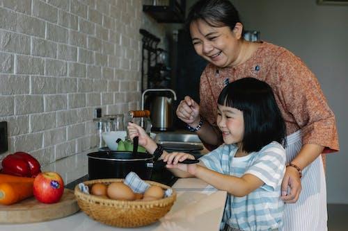 Asian woman with granddaughter preparing food