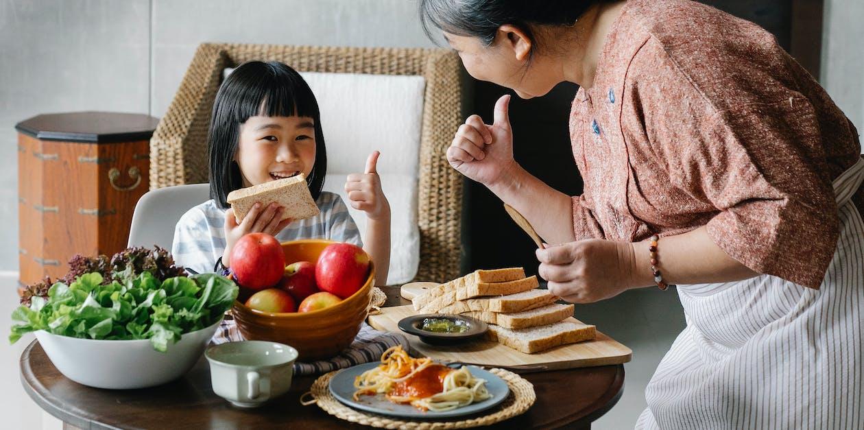 一緒に朝食をとっている孫娘と作物の女性