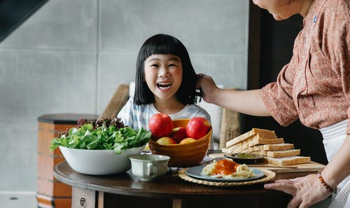 Crop unrecognizable female in apron standing near table and caressing child while having breakfast together at home