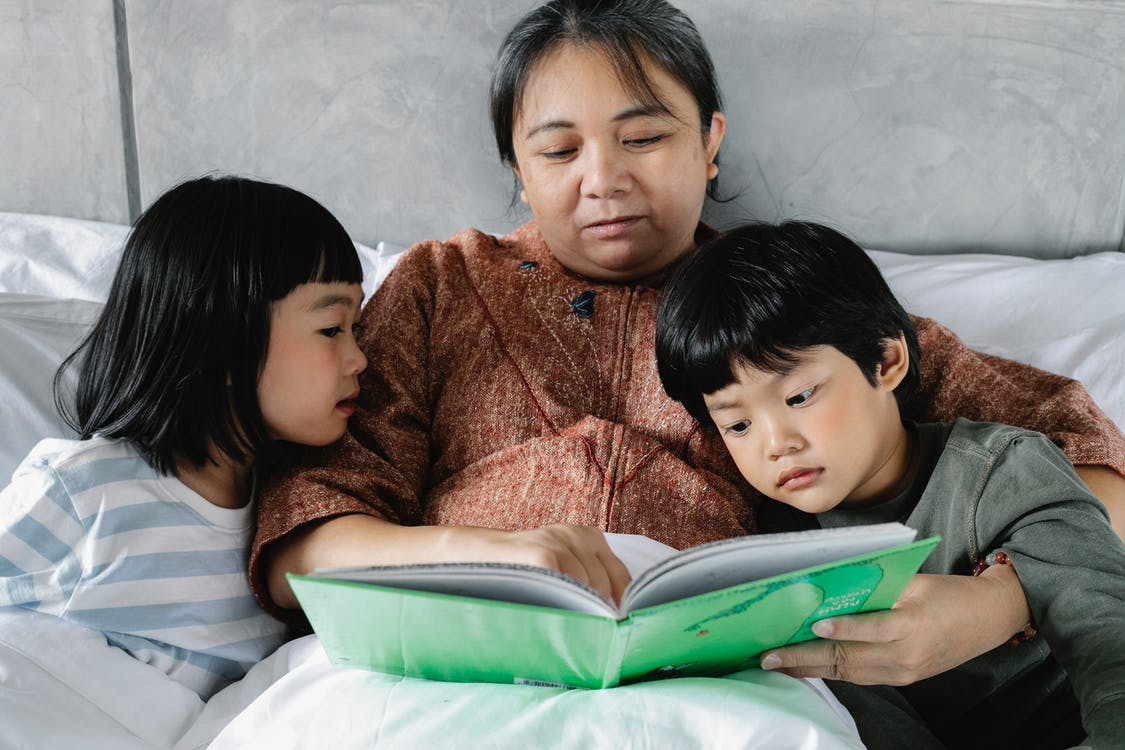 Asian grandmother reading book with children